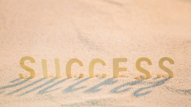 Success word with wooden alphabet put on the sand beach