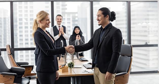 성공 작업 개념, 백그라운드에서 미소와 행복한 동료와 함께 사무실 앞의 남성과 여성 회사원의 악수.