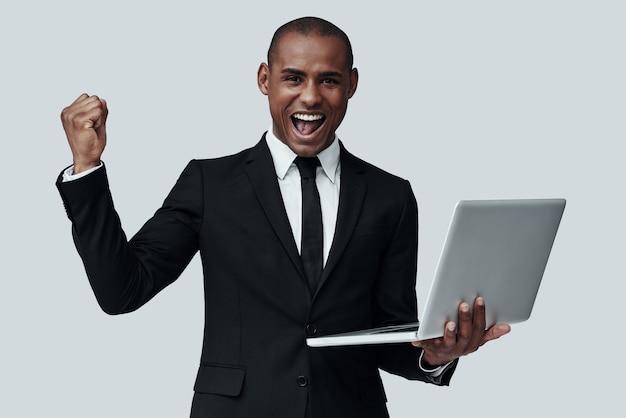 성공. 회색 배경에 서있는 동안 몸짓과 미소 formalwear에서 젊은 아프리카 남자