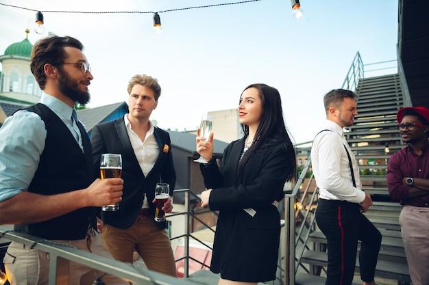成功幸せそうに見えることを祝う若者は、オフィスやバーでパーティーを開きます男性と女性