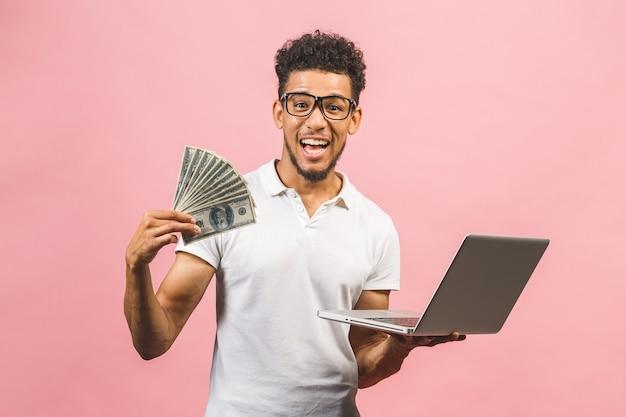 한 손에 현금, 다른 노트북을 들고 성공적인 아프리카 계 미국인 사업가