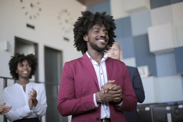 Riuscito team leader afro-americano che fa una presentazione alla riunione d'affari in un ufficio moderno