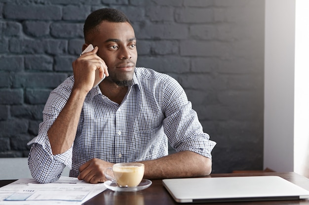Successful african businessman in shirt with rolled up sleeves having phone call