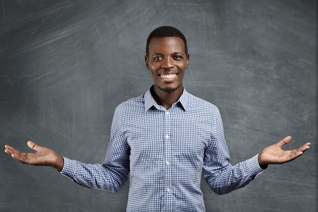 Successful african businessman with happy and confident smile dressed in blue checkered shirt holding his hands in welcoming gesture
