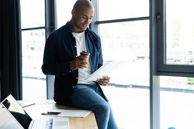 세심하고 집중된 표정으로 문서를 공부하는 성공적인 아프리카 기업가, 카페에서 커피를 마시고 있습니다. 업무 문제에 집중하고 비즈니스 거래를 위한 서류에 서명하는 검은 피부 사업가
