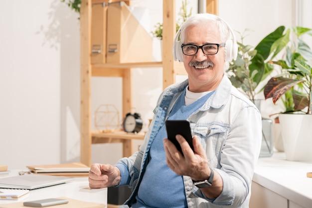 デスクで座っている間、ヘッドフォンとスマートフォンを使用してカジュアルウェアで成功した老人