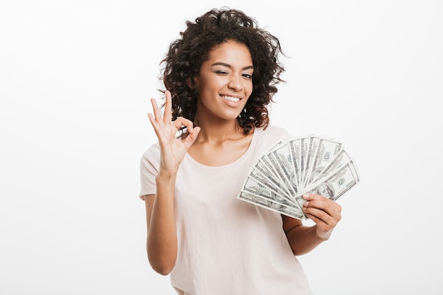 Successful american woman with curly dark hair holding fan of money dollar bills and showing ok sign, isolated over white wall