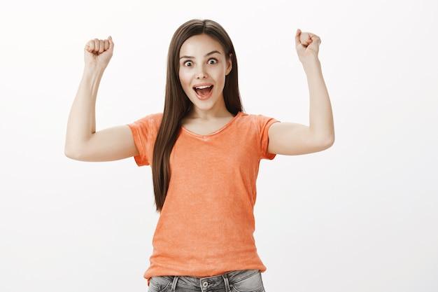 Успешная и веселая симпатичная брюнетка девушка поднимает руки вверх, кулак нагнетает ура, жест победы