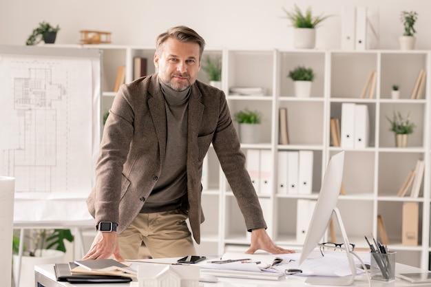 Успешный и уверенный в себе архитектор в строгой одежде, склонившись над столом с монитором компьютера и канцелярскими принадлежностями