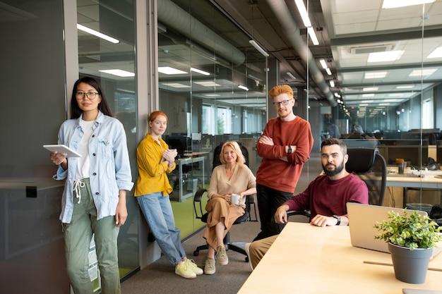 크고 현대적인 사무실에서 일하는 동안 모바일 장치를 사용하는 캐주얼웨어의 성공하고 자신감있는 사업가 및 경제인