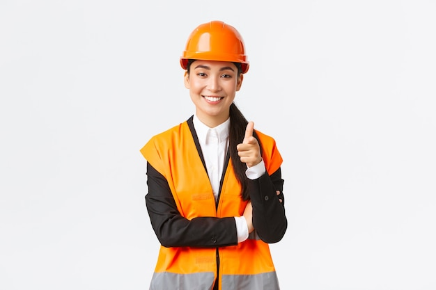 安全ヘルを身に着けているカメラに指を指している成功し、自信を持って笑顔のアジアの女性建築家...