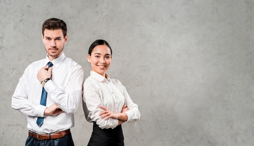 Successful and confident young businessman and businesswoman standing against grey wall
