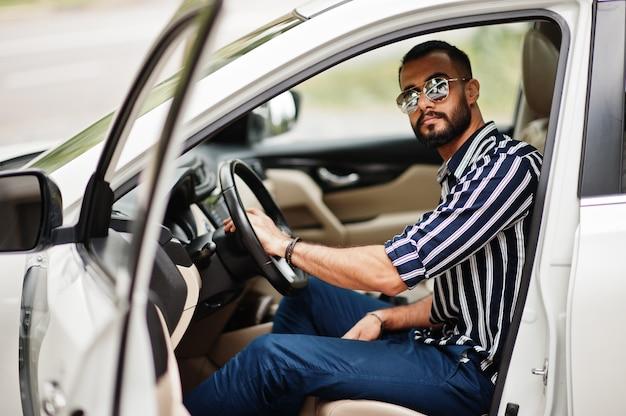 縞模様のシャツとサングラスで成功したアラブ人は、彼の白いsuv車のハンドルの後ろでポーズをとります。輸送中のスタイリッシュなアラビア人男性。