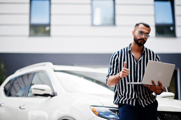 成功したアラブ人は、ラップトップを手に、白いsuvの車の近くでストライプのシャツとサングラスを着用しています。