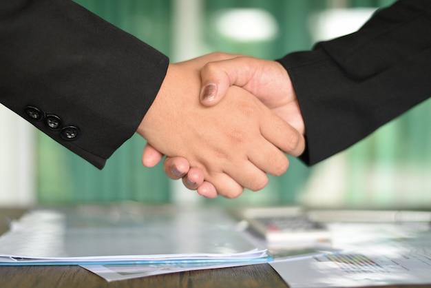 Успешные азиатские деловые женщины пожимают друг другу руки нуждающимся в обмене и сотрудничестве