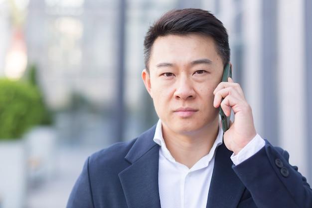 현대적이고 진지하며 생각에 잠긴 큰 직원의 사무실 근처를 걷는 동안 휴대폰으로 통화하는 성공적인 아시아 사업가