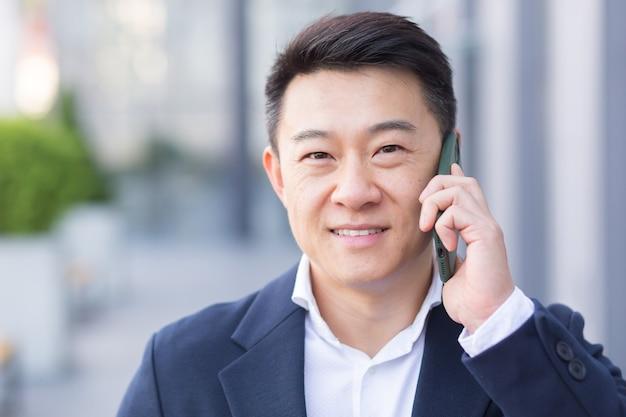 큰 현대 사무실 근처를 걷는 동안 휴대폰 통화를 하는 성공적인 아시아 사업가, 쾌활한 웃는 직원, 카메라를 바라보는