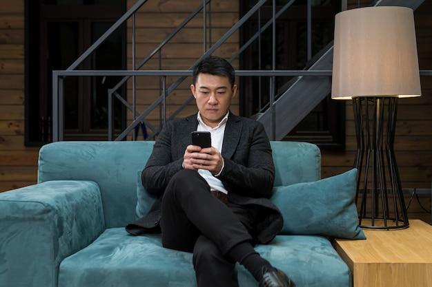 Успешный азиатский бизнесмен в черном деловом костюме пользуется телефоном