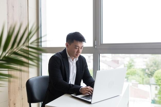 黒のビジネススーツで成功したアジアのビジネスマンは、スタイリッシュなオフィスでラップトップで動作します
