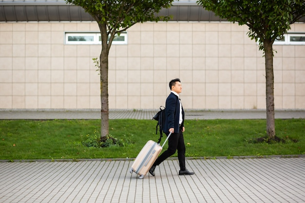 공항과 버스 정류장 근처의 성공적인 아시아 사업가는 카메라를 보고 있는 진지한 관광객을 여행 가방과 함께 간다
