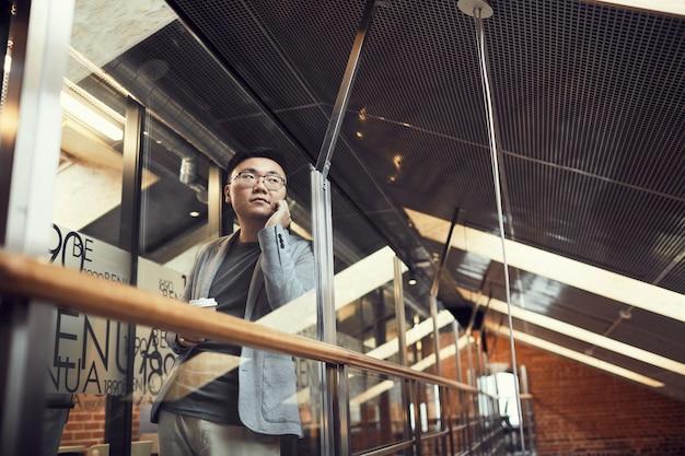 Успешный азиатский бизнесмен, выступая на смартфон в офисе
