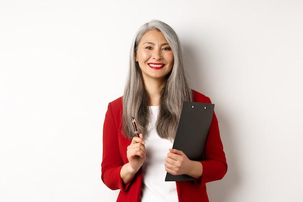 Capo di donna asiatica di successo in giacca rossa, che tiene appunti con documenti e penna, lavora e sembra felice, sfondo bianco.