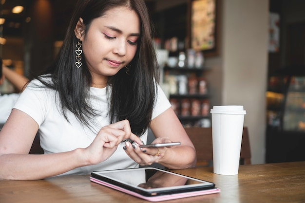 Successful asian woman using smartphone for online business at coffee cafe.