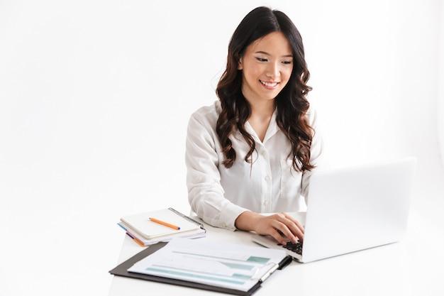 긴 검은 머리가 테이블에 앉아 문서와 노트북을 사용하여 성공적인 아시아 여자