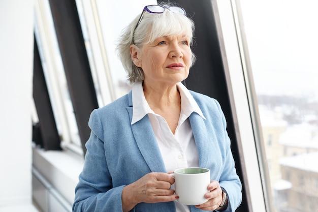 Architetto femminile maturo attraente di successo che indossa occhiali sulla sua testa e abito formale godendo di una piccola pausa, bevendo caffè dalla finestra, tenendo la tazza e guardando con espressione facciale premurosa