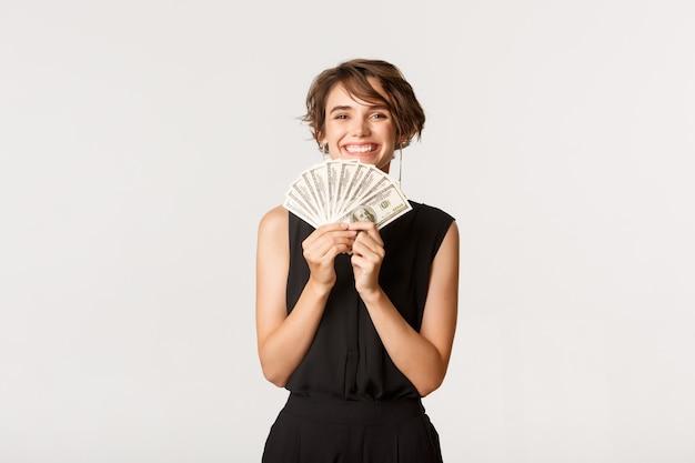 Успешная привлекательная женщина показывает деньги, довольные улыбкой, стоя над белой.