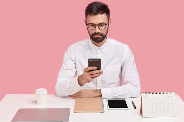 Capo barbuto di successo in camicia bianca formale, tiene il telefono cellulare, compone il numero di telefono, cerca informazioni nel browser, essendo perfezionista