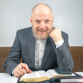 Successful bearded businessman studying the bible while doing business