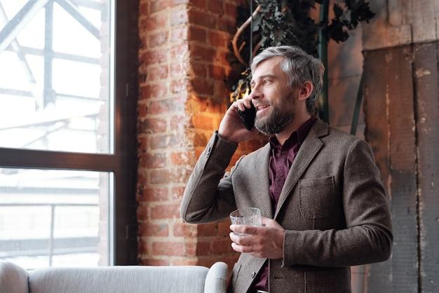 Успешный бородатый предприниматель в куртке стоит в лофт-студии и обсуждает сделку по телефону, попивая алкоголь