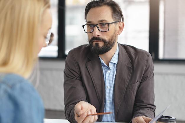 成功したひげを生やした男性の雇用主が仕事のために女性にインタビュー