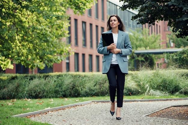 문서를 들고 현대 사무실 근처 회의장까지 걸어가는 정장을 입은 성공적인 아름다운 비즈니스 여성