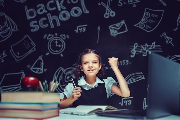 Успешный красивый ученик сидит за столом и учится онлайн с ноутбуком на черном фоне
