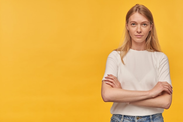 手を組んで立っている白いtシャツのそばかすと黄色に自信を持って見える成功した美しい女性