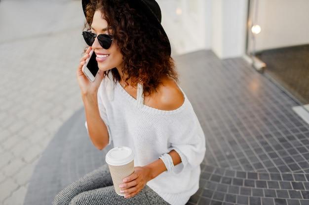 コーヒーブレーク中に携帯電話で話している成功した黒人女性、ブロガー、または店長。
