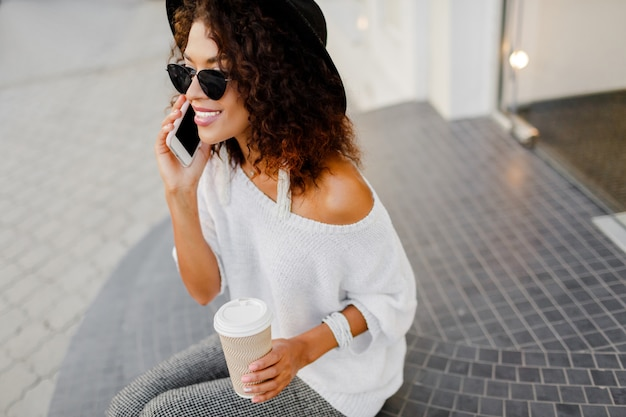 Successful black woman, blogger or store manager  talking by mobile phone during coffee break.