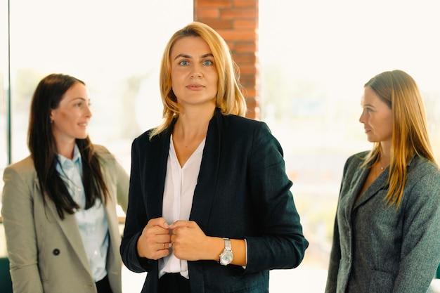 그녀의 동료 근처 새 사무실에서 성공적인 blondine 비즈니스 여자. 현대 시작 사무실 인테리어, 회의에서 팀에서 젊은 비즈니스 숙 녀의 초상화.