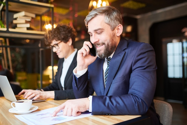 Successful broker in elegant suit analyzing charts on papers while talking to colleague or client on smartphone