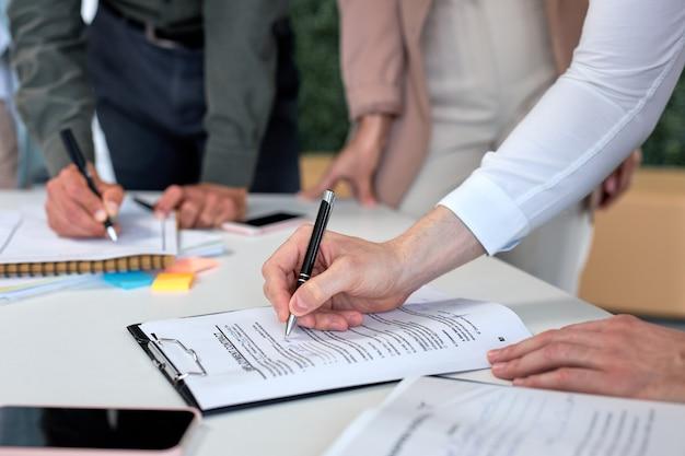 成功するビジネス契約、取引コンセプト。同僚の同僚の前で現代の明るいオフィスの机の上にペンで公式契約書、正式な文書に署名するトリミングされたビジネスマン