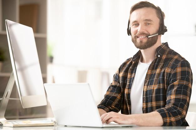 Deskaのそばに座り、クライアントとコミュニケーションを取り、ネットで閲覧する成功したビジネスコンサルタント