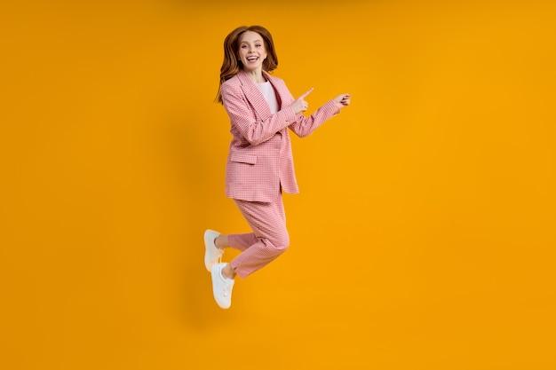 Успешная бизнес-леди в розовом костюме прыгает, прикрепляя указательный палец сбоку, изолированном на желтом фоне, делая покупки. портрет. копировать место для рекламы