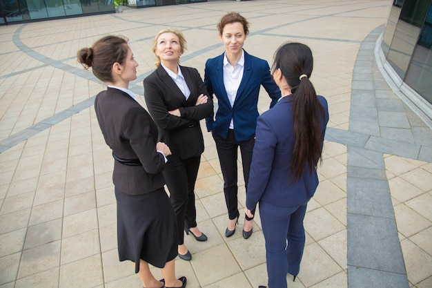 Successful business ladies talking outdoors. businesswomen wearing suits standing together in city. low angle. work discussion and teamwork concept