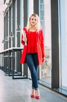 窓際の軽いオフィスビルで赤いスーツを着たビジネスウーマン