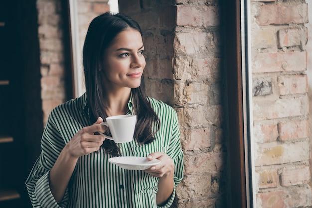 Успешная бизнес-леди смотрит в окно пить кофе в офисе