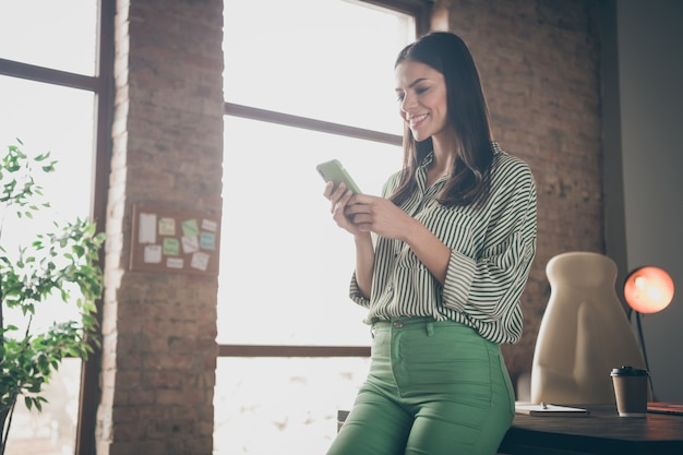 Successful business lady using cell phone at modern industrial loft