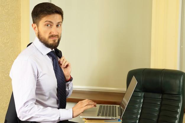 Успешный деловой человек в офисе с ноутбуком