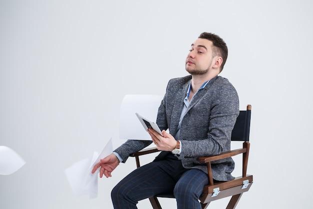 書類のフォルダーと木製の椅子に座って、それらを空中に投げるスーツで成功したビジネスマンのビジネスマン。新しいプロジェクトの考えと白い背景に